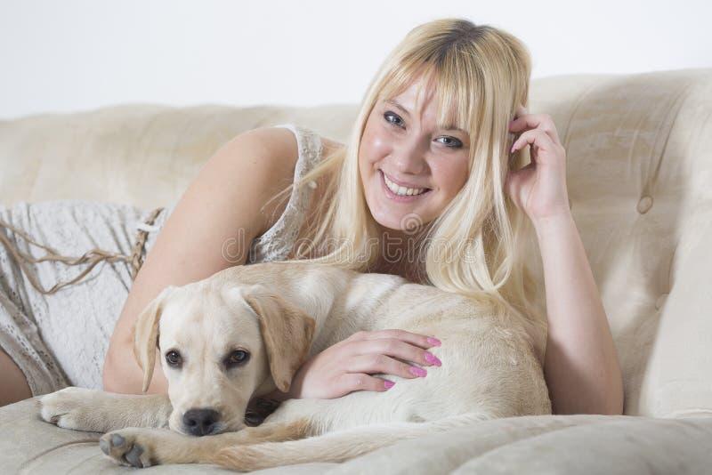 Mulher que senta-se no sofá branco com cachorrinho de Labrador fotografia de stock royalty free