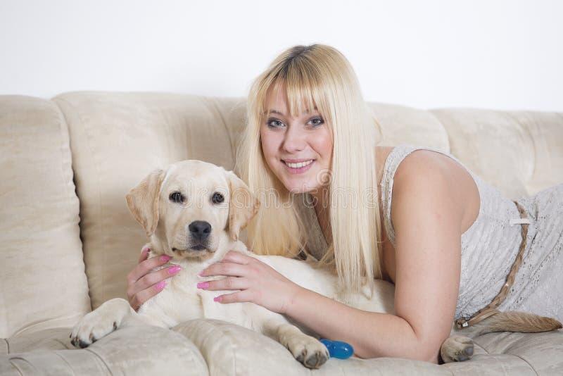 Mulher que senta-se no sofá branco com cachorrinho de Labrador fotos de stock