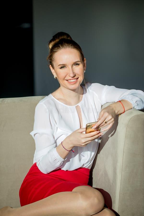 Mulher que senta-se no sofá branco que verifica seu smartphone foto de stock