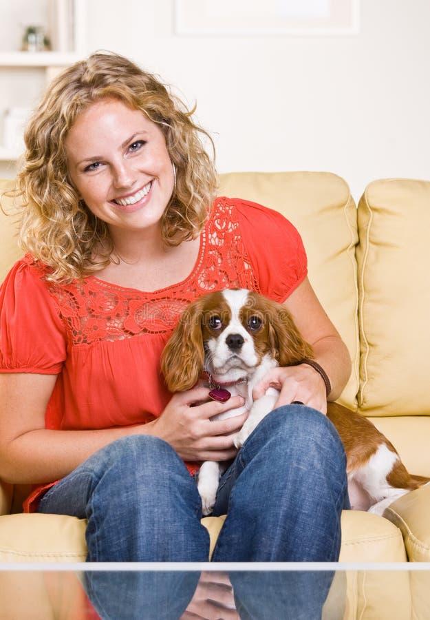 Mulher que senta-se no sofá com cão fotografia de stock royalty free
