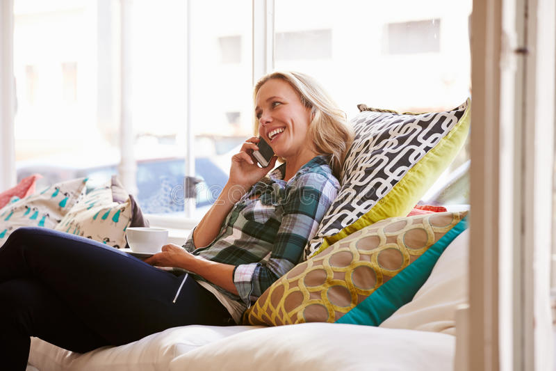 Mulher que senta-se no sofá em um café foto de stock