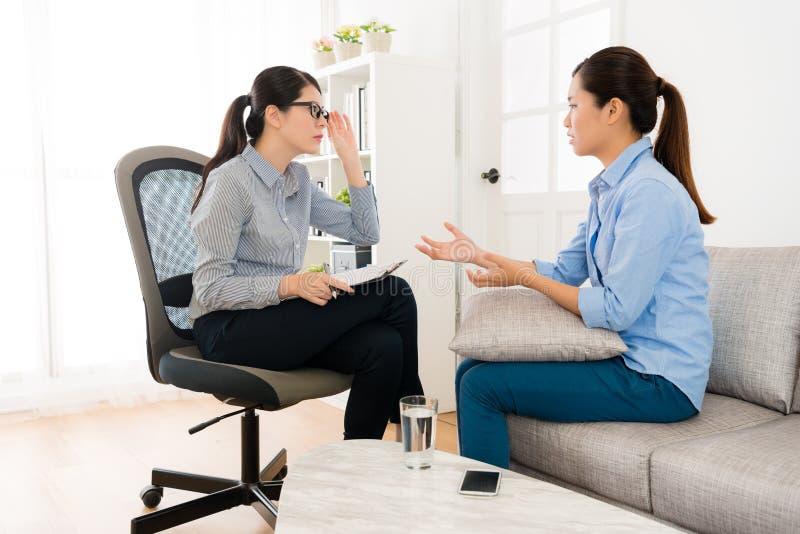 Mulher que senta-se no sofá que fala com seu doutor imagens de stock royalty free