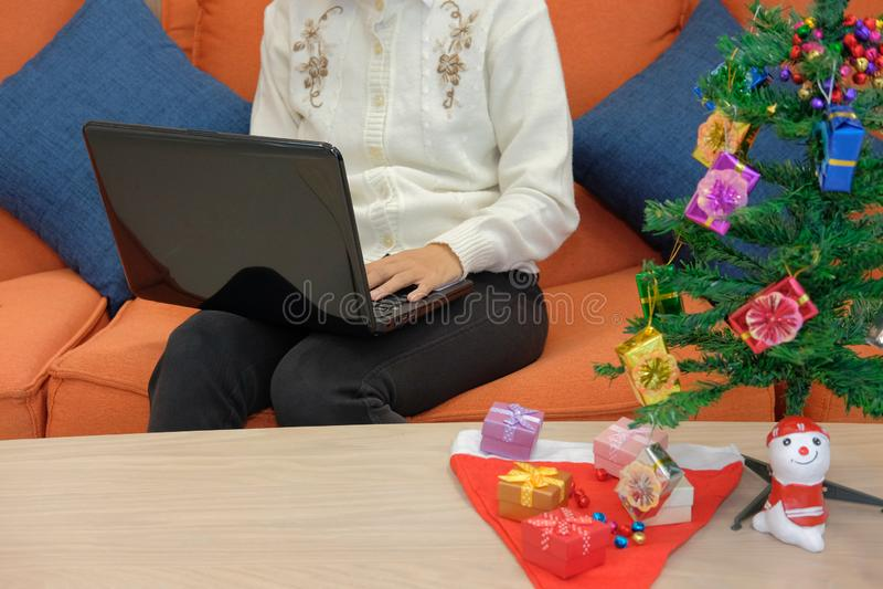 mulher que senta-se no sofá usando o computador durante o xmas Holi do Natal imagem de stock royalty free