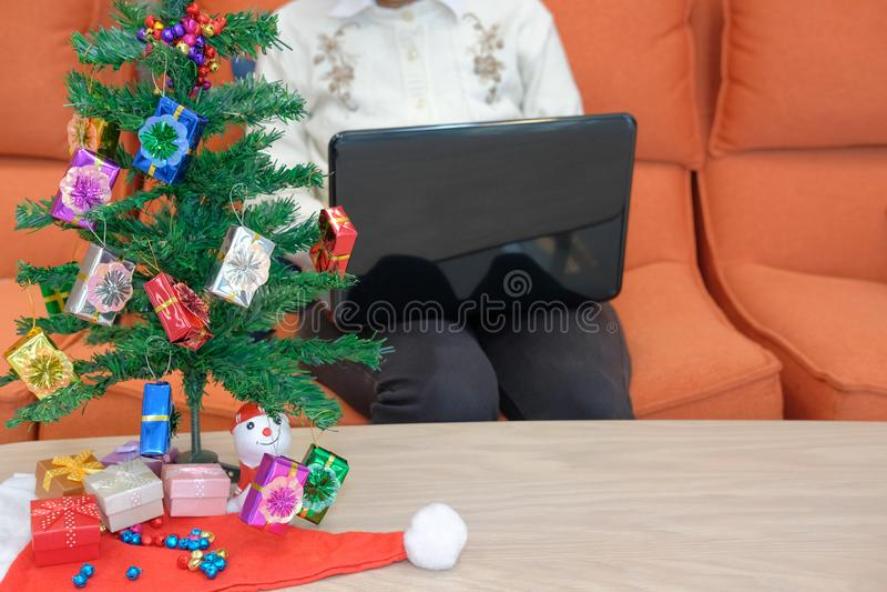 mulher que senta-se no sofá usando o computador durante o xmas Holi do Natal fotografia de stock royalty free