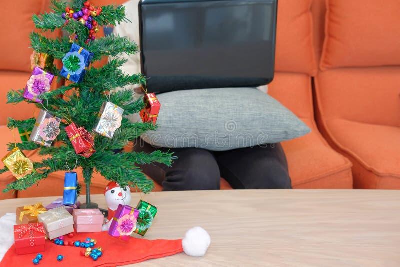 mulher que senta-se no sofá usando o computador durante o xmas Holi do Natal imagem de stock