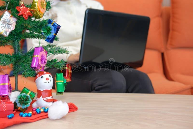 mulher que senta-se no sofá usando o computador durante o xmas Holi do Natal fotografia de stock