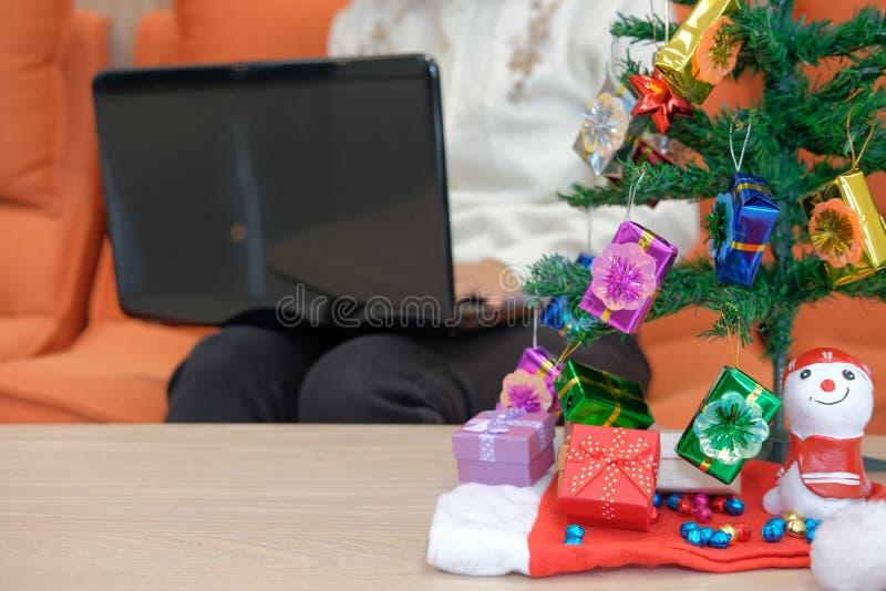 mulher que senta-se no sofá usando o computador durante o xmas Holi do Natal fotos de stock