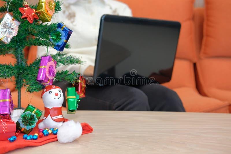 mulher que senta-se no sofá usando o computador durante o xmas Holi do Natal foto de stock royalty free