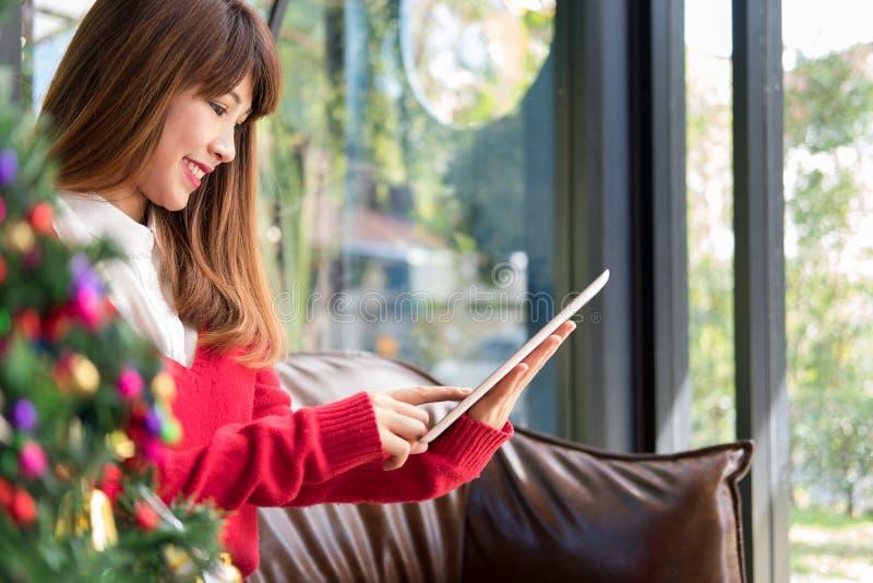 Mulher que senta-se no sofá usando o PC da tabuleta em casa confusão texting da menina imagem de stock royalty free