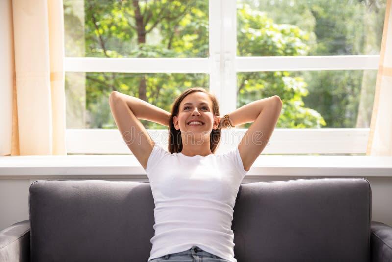Mulher que senta-se no sof? imagem de stock royalty free