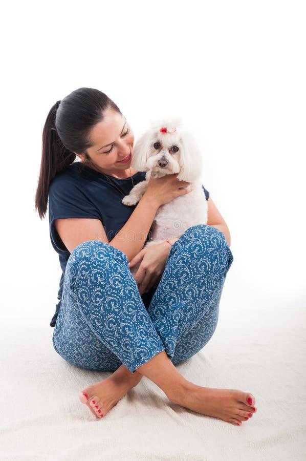 Mulher que senta-se no tapete com um cão fotos de stock