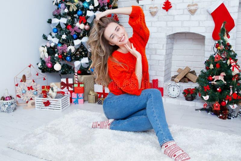 Mulher que senta-se no tapete no Natal em casa na sala de visitas, na celebração do ano novo, na árvore de Natal e na chaminé dec fotografia de stock