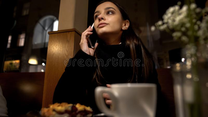 Mulher que senta-se no telefone de fala do caf? com noivo tarde para a data, relacionamento imagens de stock royalty free