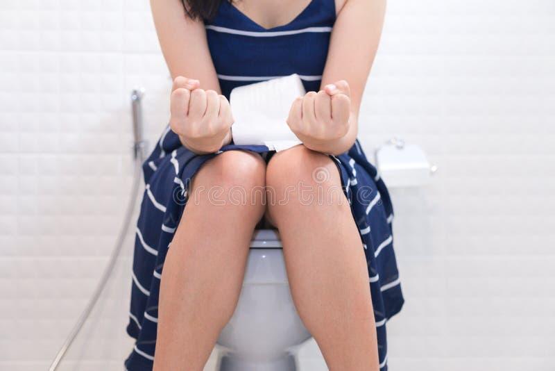 Mulher que senta-se no toalete com papel higiênico - conceito da constipação imagens de stock