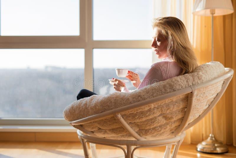 Mulher que senta-se pela janela e pelo chá bebendo imagem de stock