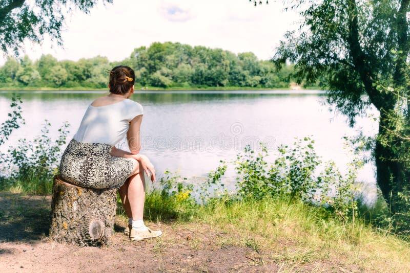 Mulher que senta-se perto do rio imagens de stock royalty free