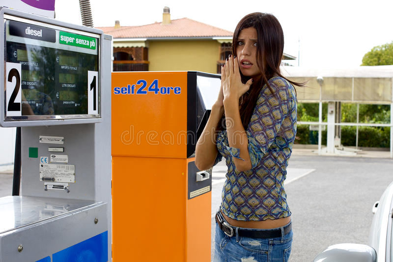Mulher que sente má para o preço alto da gasolina imagens de stock royalty free