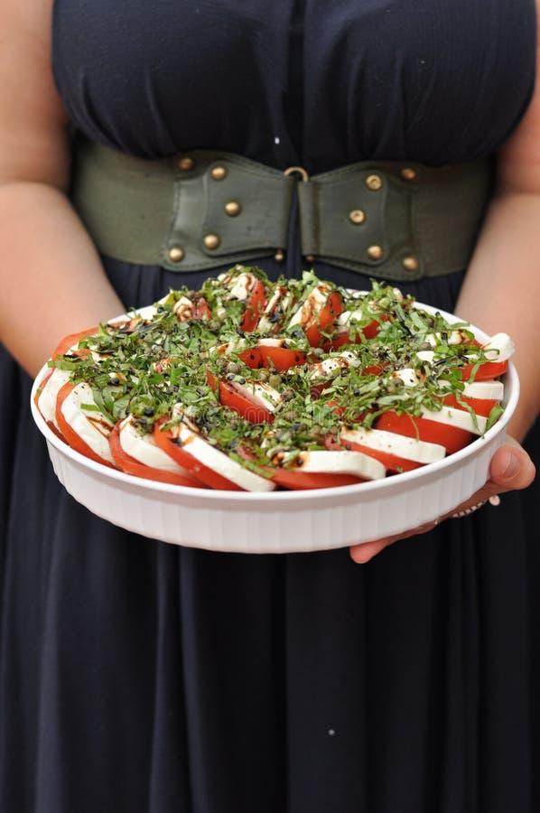 Mulher que serve a salada de Caprese imagem de stock