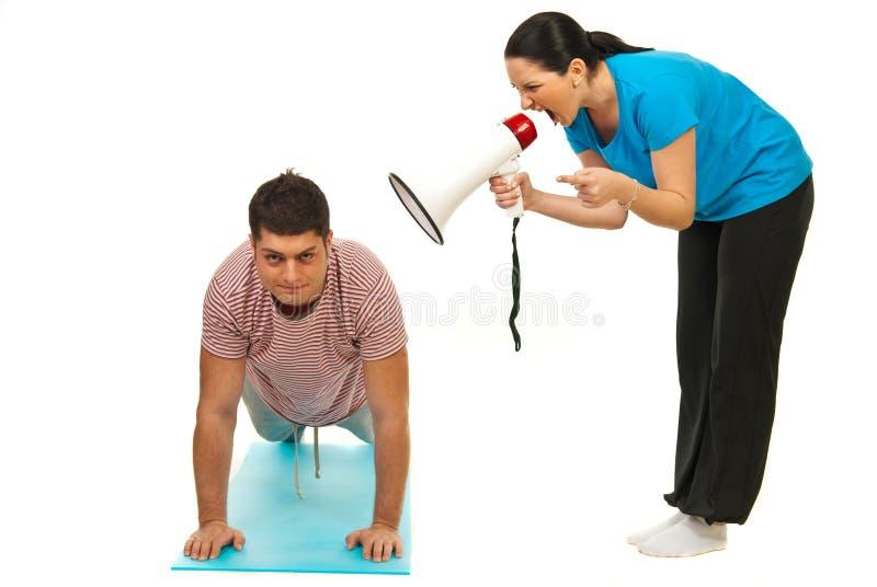 Mulher que shouting pelo megapone ao homem do exercício fotos de stock