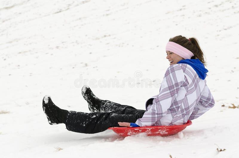 Mulher que sledding abaixo do monte nevado 2 foto de stock
