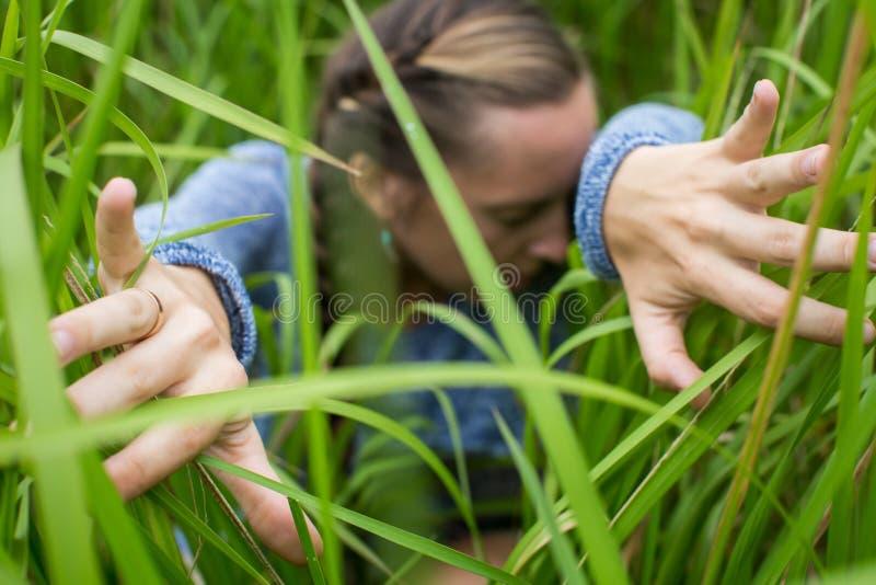 Mulher que sneaking através da grama foto de stock
