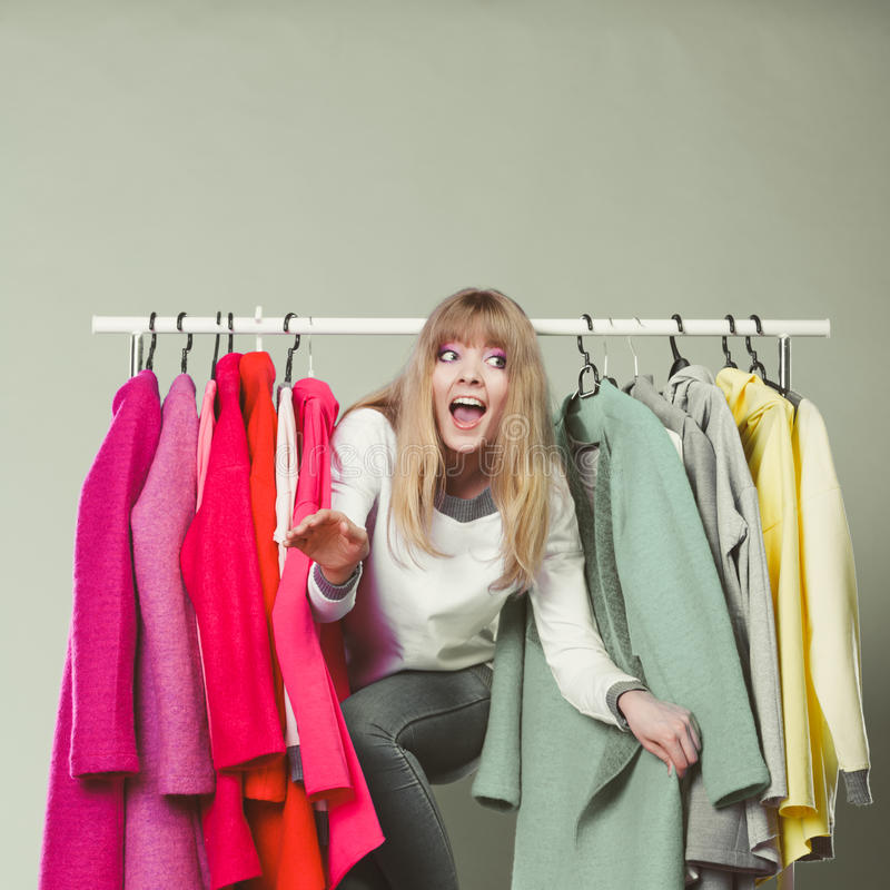 Mulher que sneaking entre a roupa na alameda ou no vestuário imagens de stock