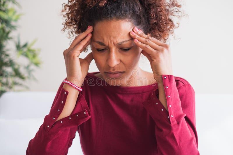 Mulher que sofre da dor de cabeça terrível que faz massagens templos fotos de stock