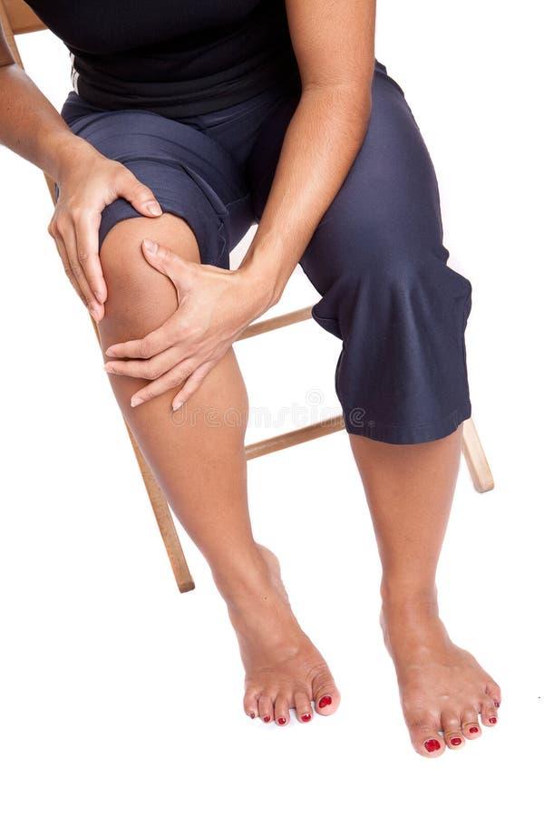 Mulher que sofre da dor em seu joelho imagem de stock