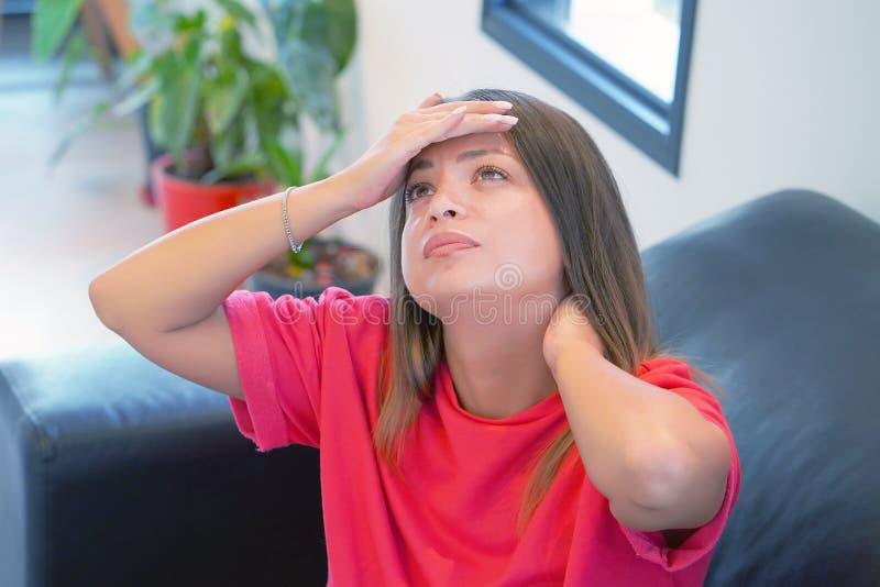 Mulher que sofre da dor da enxaqueca da dor de cabeça em casa no sofá Problema de saúde, esforço e depressão fotografia de stock
