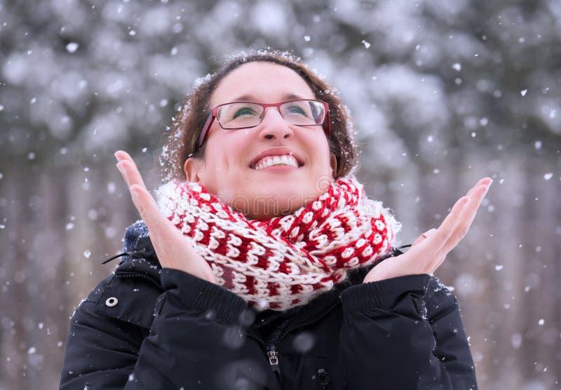 A mulher que sorri alegremente com mãos acima como a neve do inverno cai para baixo, fotografia de stock