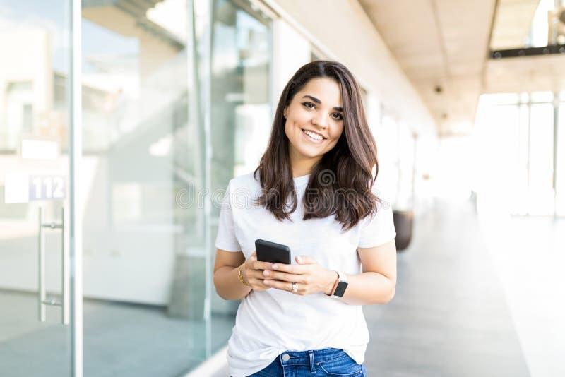Mulher que sorri ao guardar o telefone celular no shopping fotografia de stock