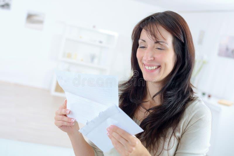 Mulher que sorri ao ler a letra fotografia de stock royalty free