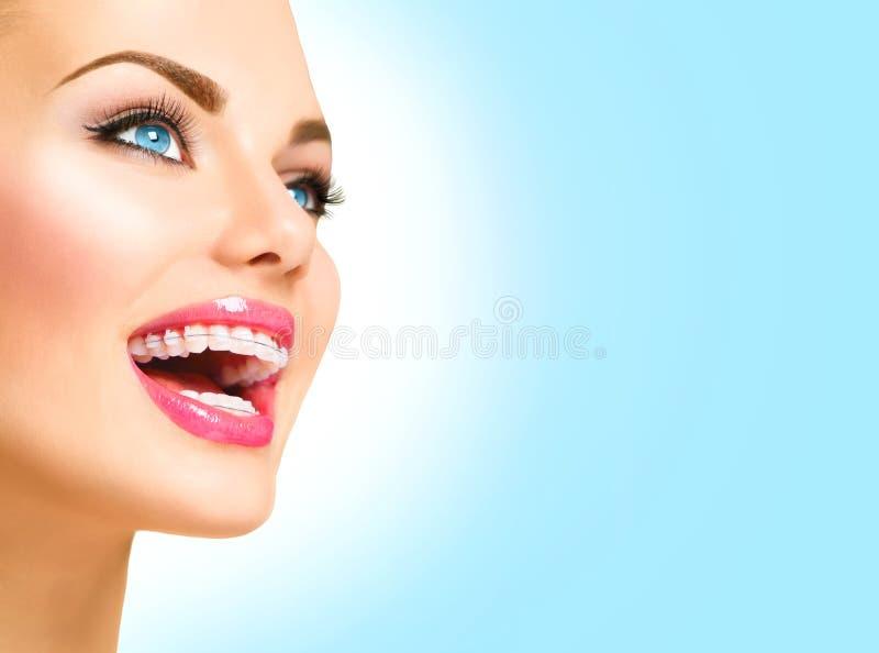 Mulher que sorri com as cintas cerâmicas nos dentes fotografia de stock