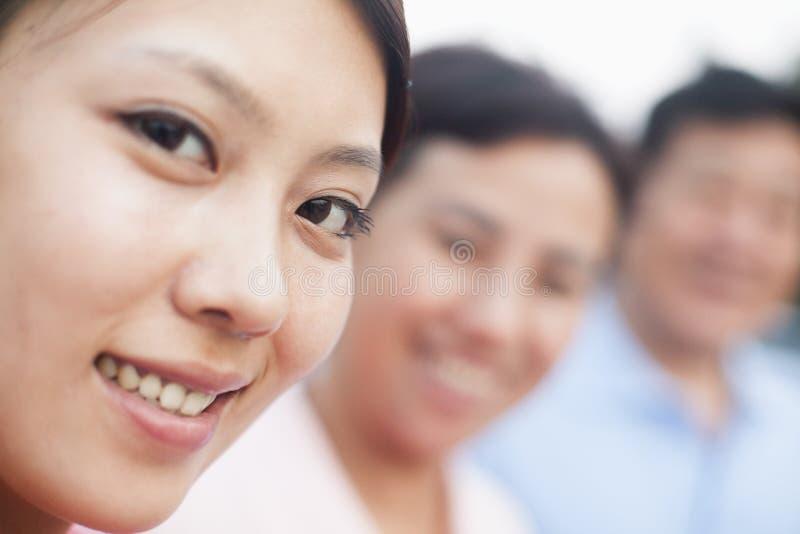 Mulher que sorri com seus pais, retrato fotos de stock