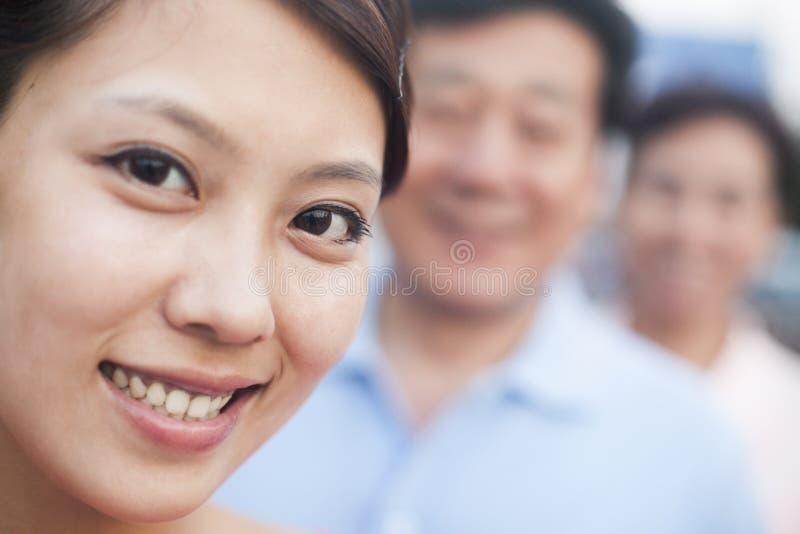 Mulher que sorri com seus pais, retrato, foco no primeiro plano imagens de stock royalty free
