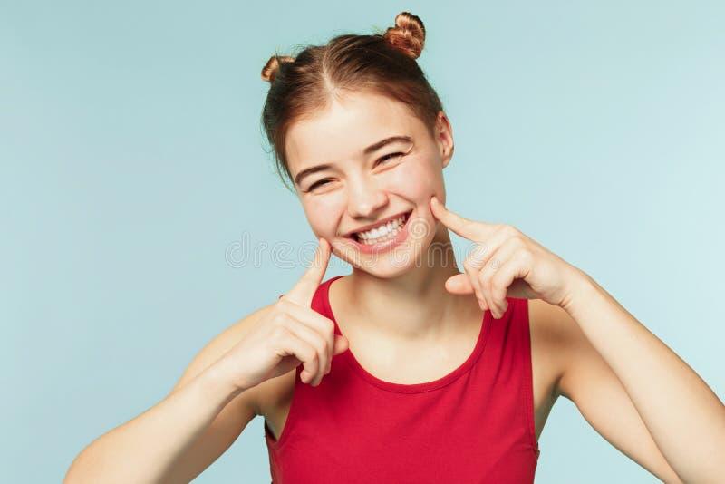 Mulher que sorri com sorriso perfeito no fundo azul do estúdio fotografia de stock