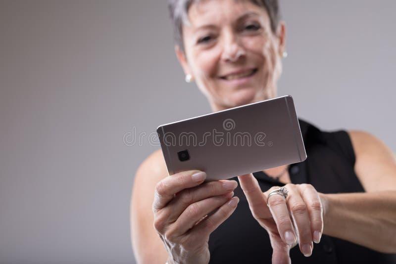 Mulher que sorri como datilografa em seu telefone celular fotos de stock royalty free