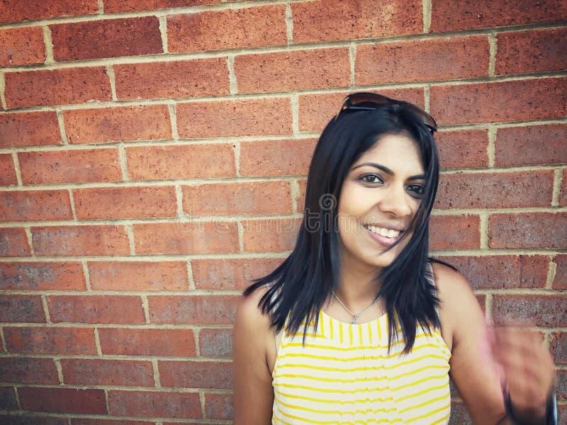 Mulher que sorri contra o fundo da parede de tijolo imagens de stock