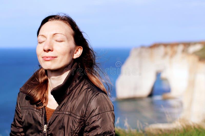 A mulher que sorri fazendo a respiração exercita sobre penhascos de normandy na primavera fotografia de stock