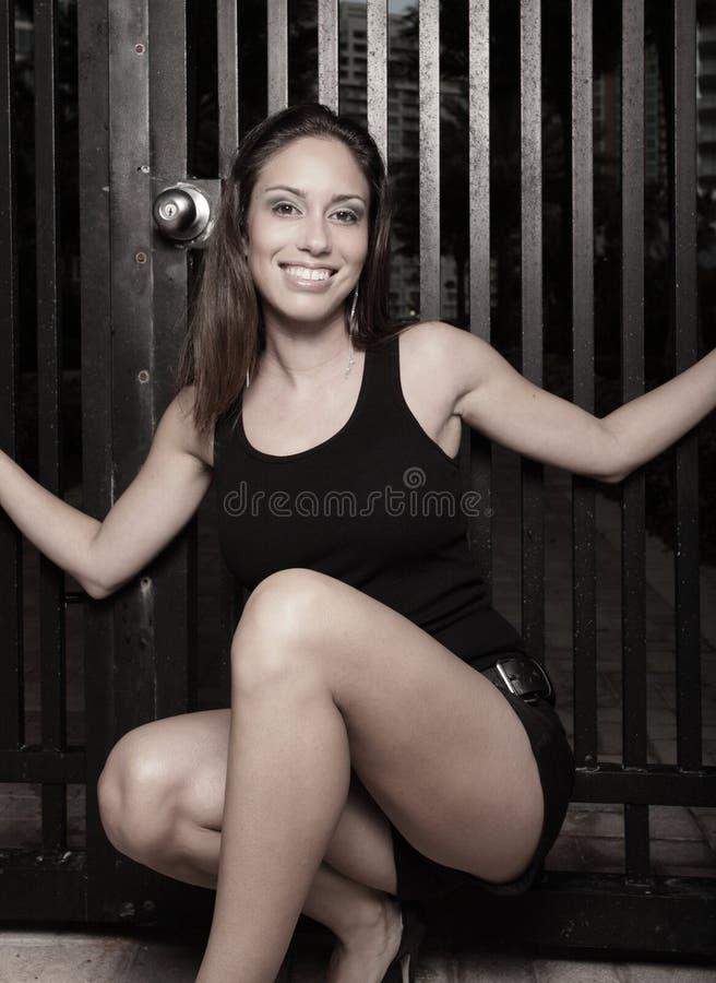 Mulher que squatting e que sorri fotos de stock
