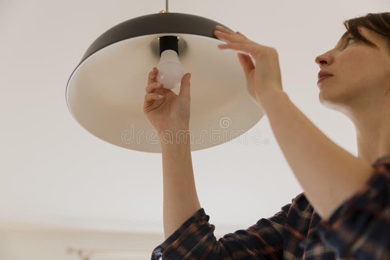 Mulher que substitui a ampola em casa Mudança da lâmpada do diodo emissor de luz da economia de energia foto de stock