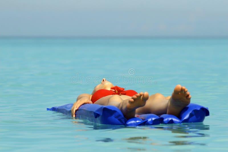 Mulher que sunbathing em um colchão de ar foto de stock royalty free