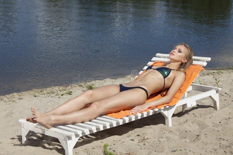 Mulher que sunbathing na praia imagens de stock