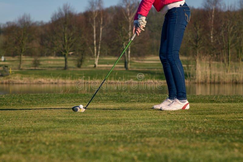 Mulher que teeing fora em um campo de golfe fotografia de stock royalty free
