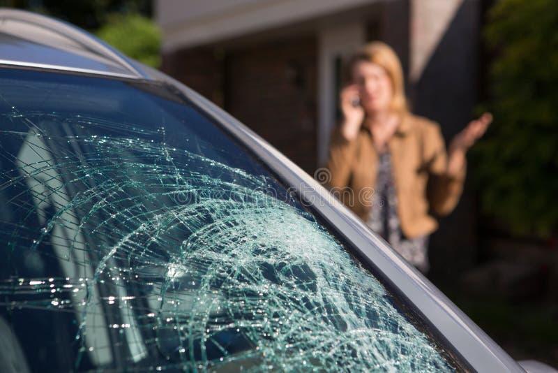 A mulher que telefona para a ajuda após o para-brisa do carro quebrou fotografia de stock royalty free