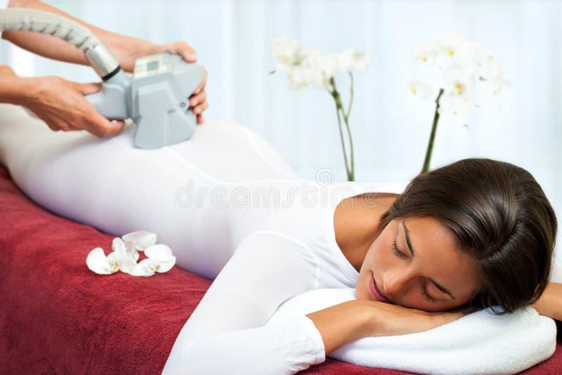 Mulher que tem a anti massagem do vibro das celulites. foto de stock