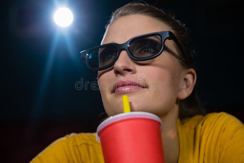 Mulher que tem bebidas ao olhar o filme no teatro imagens de stock