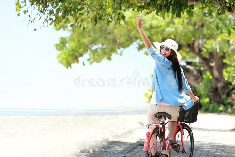 Mulher que tem a bicicleta da equitação do divertimento na praia imagens de stock