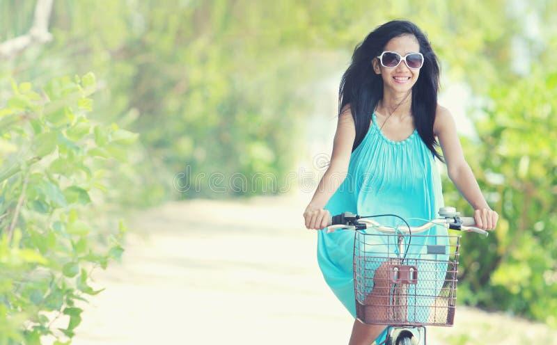 Mulher que tem a bicicleta da equitação do divertimento na praia fotografia de stock