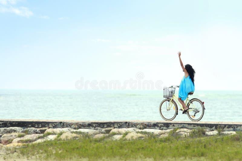 Mulher que tem a bicicleta da equitação do divertimento na praia fotos de stock royalty free